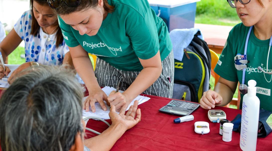 Durante una brigada médica en Filipinas, una voluntaria ayuda a medir la glucosa.